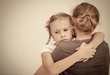 Mulher de costas para a câmera, segurando uma menina em seu colo, abraçada. A menina está com uma expressão preocupada.