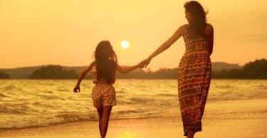 Mãe e filha caminhando na praia