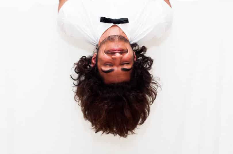 Homem de cabeça para baixo sorrindo e com os olhos fechados