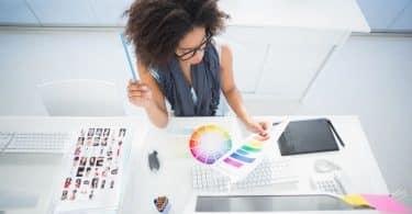 Mulher em mesa de trabalho analisando paleta de cores