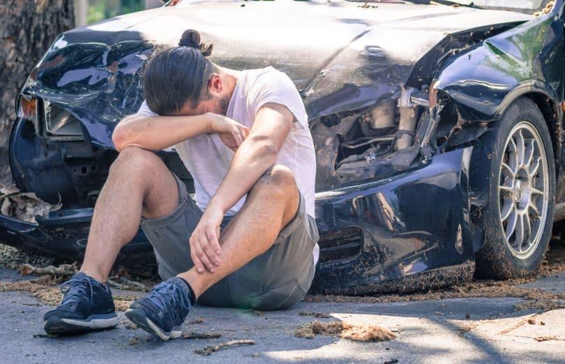 Homem triste chorando após acidente de carro.