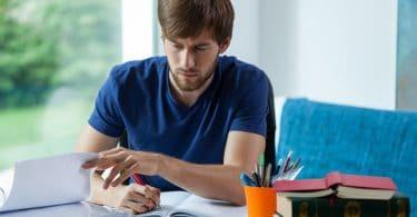 Homem sentando em frente de um caderno, escrevendo nele.