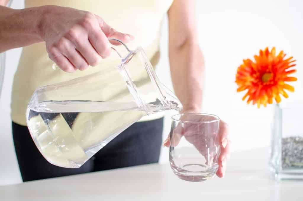 Imagem de uma mulher segundado uma jarra com água. Ela está se servindo. Ao lado uma flor laranja compõe a imagem.