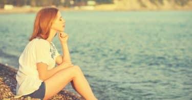 Mulher sentada em beira da praia em pedras de olhos fechados