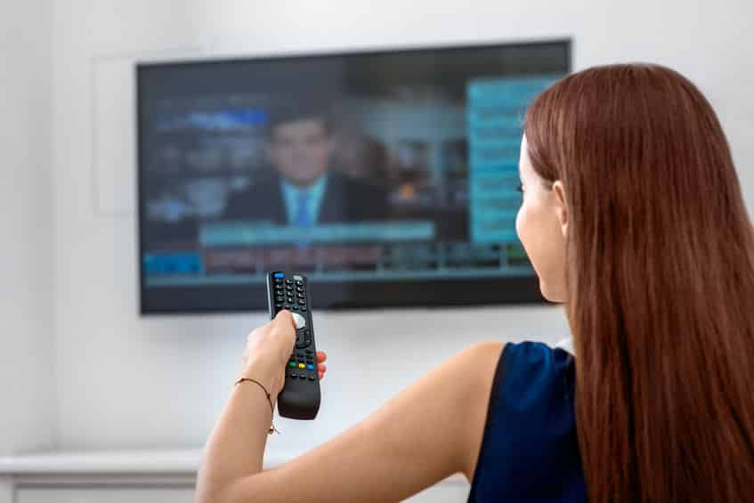 Mulher de costas para a câmera, assistindo um noticiário na televisão e segurando um controle remoto.