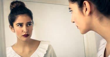 Mulher se olhando no espelho com expressão séria.