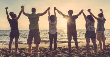 Grupo de jovens em uma praia com as mãos dadas para cima