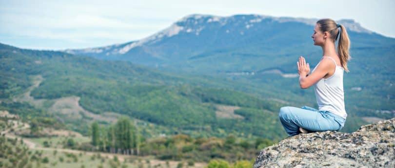 Mulher medita sobre montanhas.