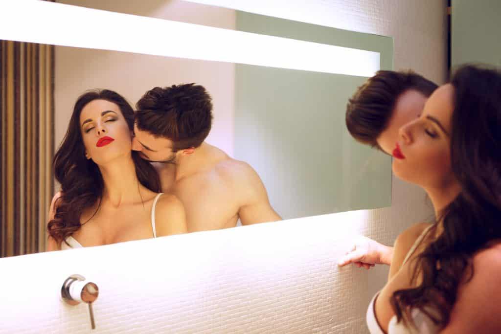 Imagem de um casal de homem e mulher. Eles estão dentro de um quarto de frente para um espelho. Ele beija o pescoço da sua companheira.