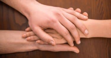 Duas mãos de uma pessoa segurando a mão de outra, sobre uma mesa de madeira