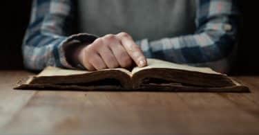 Mão apoiada em bíblia aberta sobre a mesa