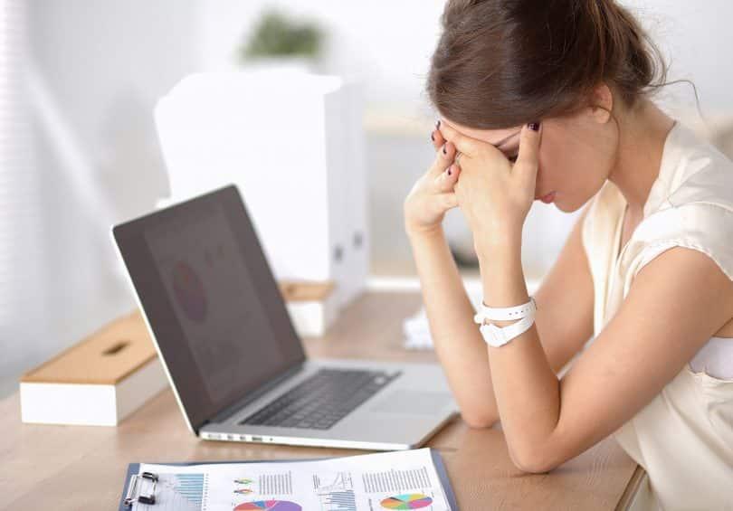 Mulher sentada em uma mesa de escritório, com a cabeça apoiada sobre as mãos, em sinal de estresse.