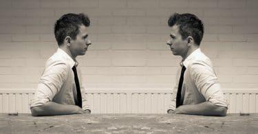 Dois homens idênticos sentados em uma bancada, um de frente para o outro.