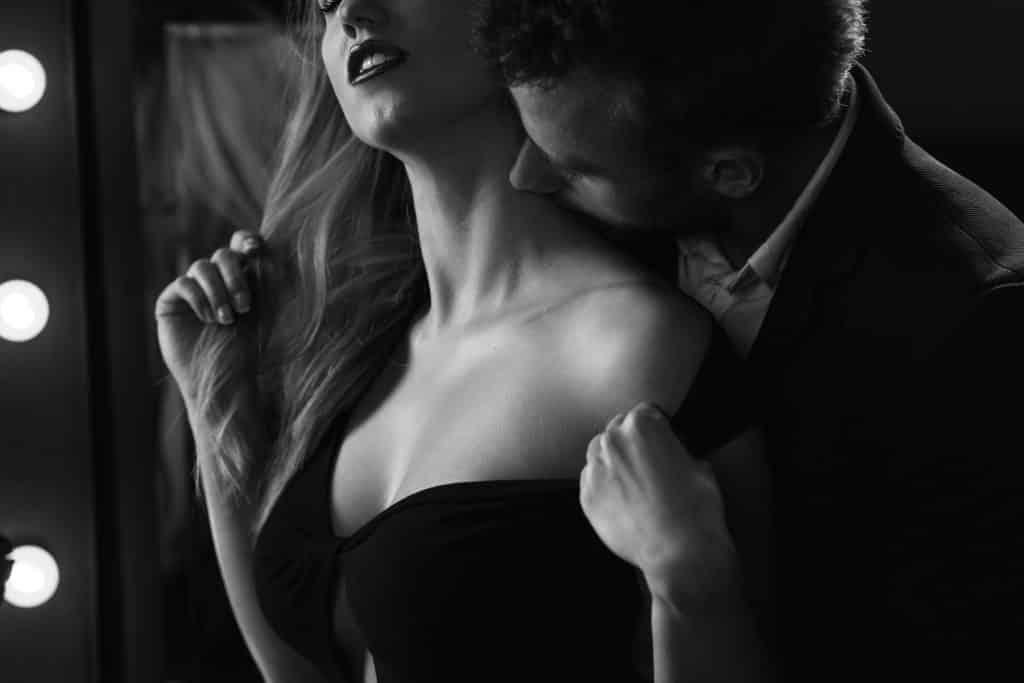 Imagem de um casal (homem e mulher). Ele veste um vestido sexy preto. Ele beija o pescoço dela de forma carinhosa.