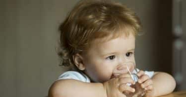 Bebê bebendo água em copo pequeno