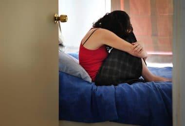Mulher sentada na cama do quarto, abraçando seus joelhos, de cabeça baixa.