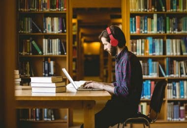 Homem sentado em uma biblioteca, estudando.