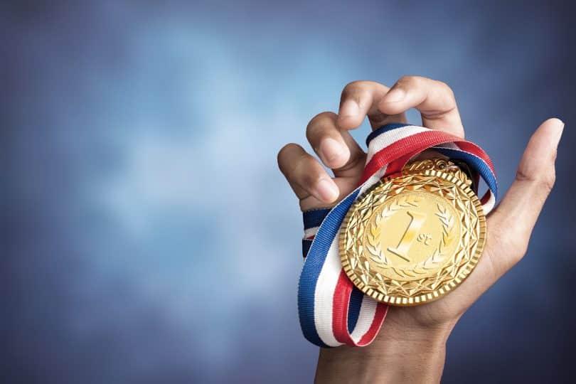 Pessoa segurando uma medalha de ouro com o número 1 em gravura.
