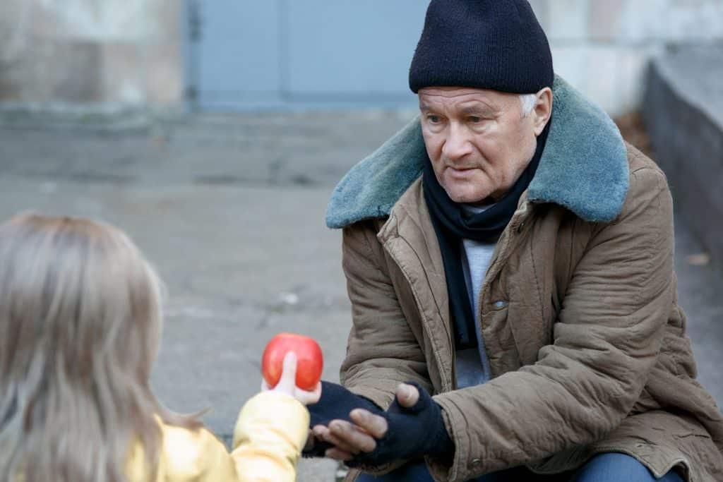 Menina dando uma maça para morador de rua