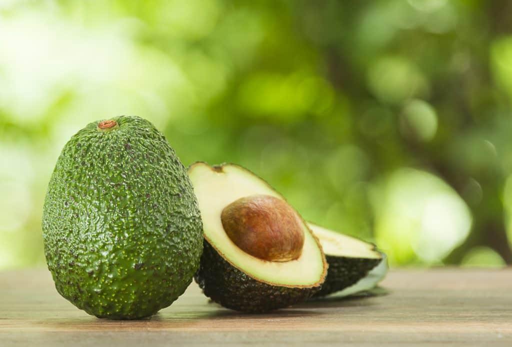 Imagem de dois abacates. Um inteiro e o outro cortado ao meio.