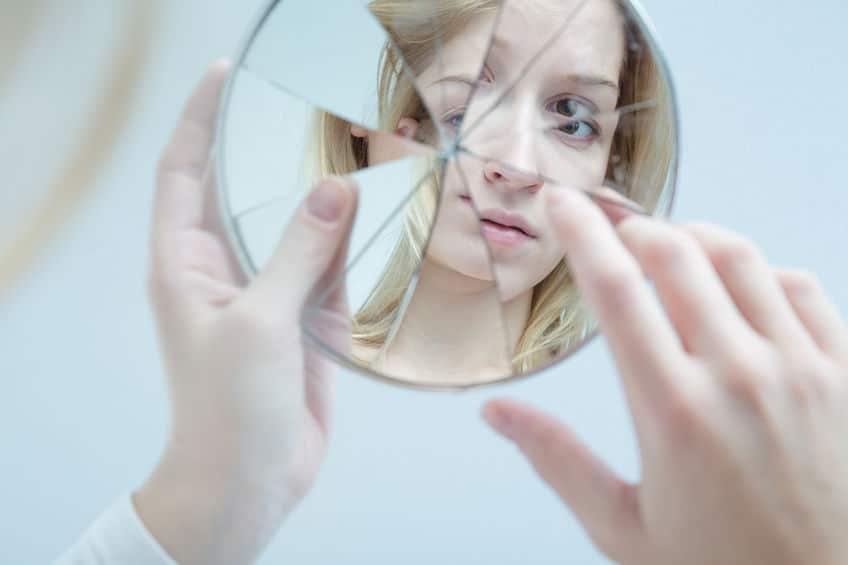 Mulher segurando espelho quebrado, olhando seu reflexo.