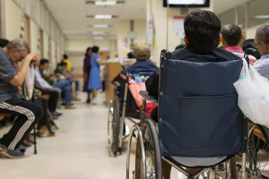 Paciente esperando doutor em uma sala de espera com muitas pessoas