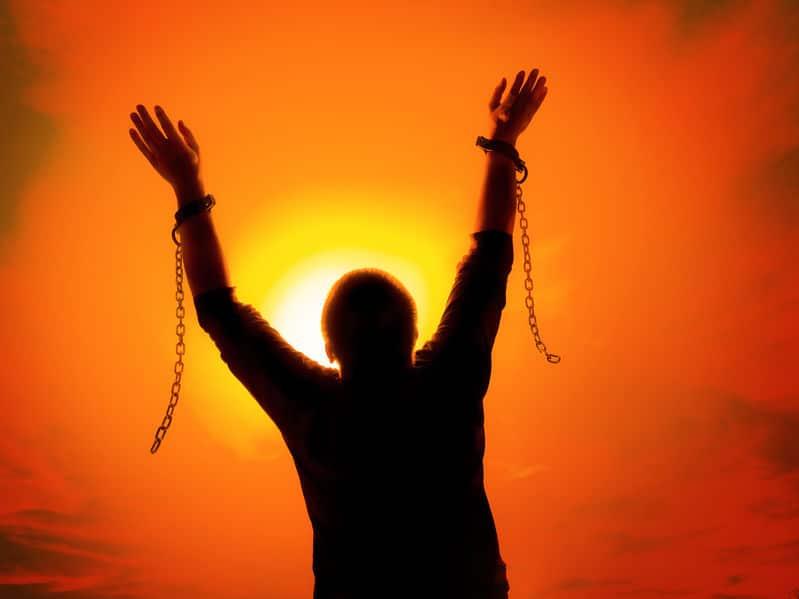 Silhueta de homem com correntes quebradas e sol ao fundo refletindo