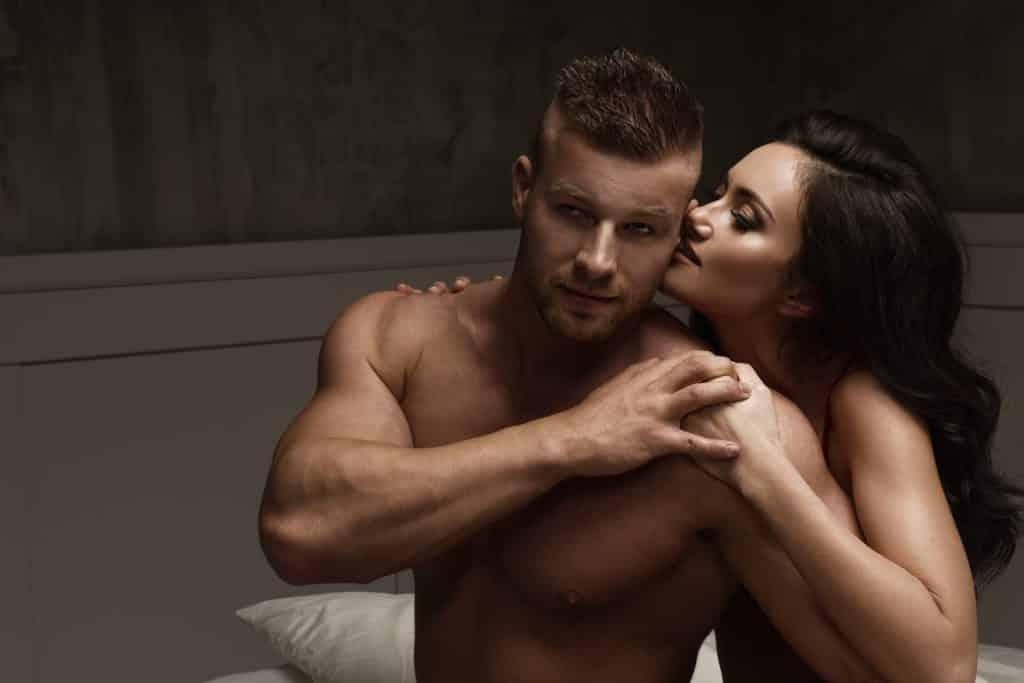 Imagem de um casal homem e mulher. Ela está beijando a orelha do parceiro e ele segura as mãos dela.