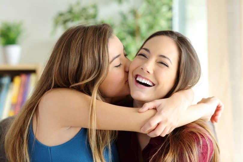 Amiga beijando no rosto de amiga
