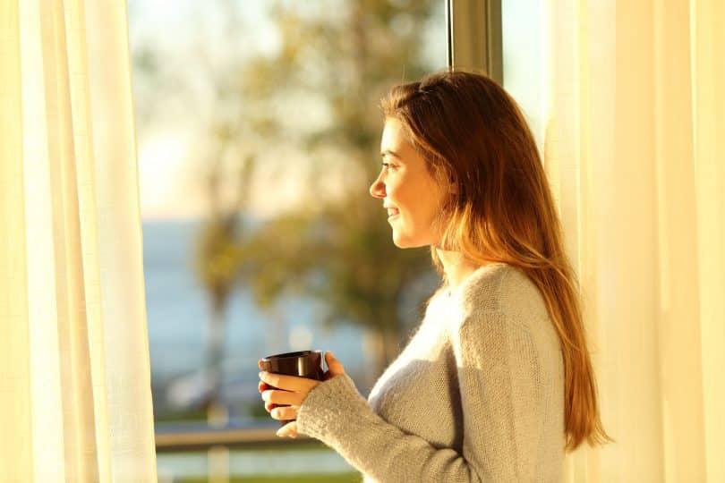 Mulher olhando para fora da janela sorrindo e segurando uma xícara