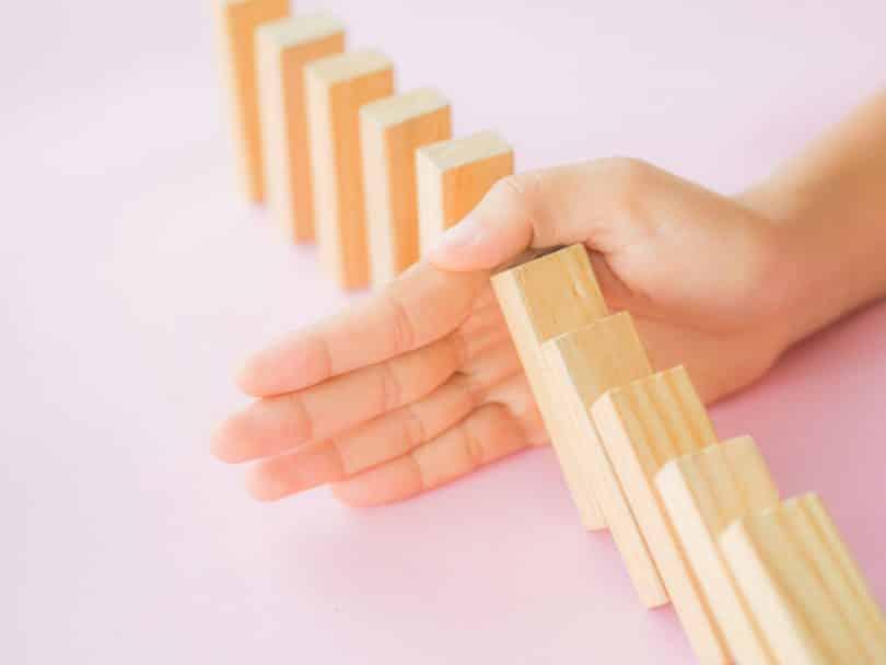 Pessoa impedindo que os dominós caem