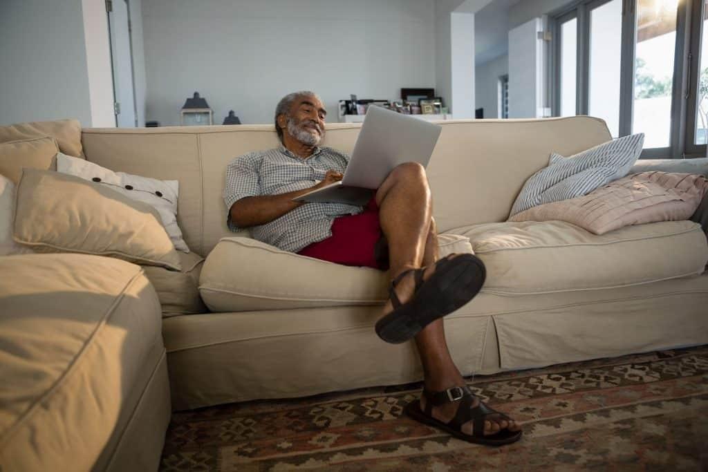 Senhor sentado em um sofá com um notebook no colo.