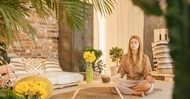 Mulher sentada no chão, de olhos fechados, meditando em sua sala e estar.
