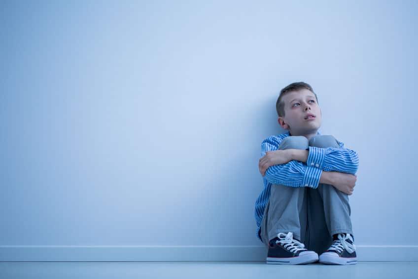 Menino sentado no chão, abraçando suas pernas e olhando para o lado.