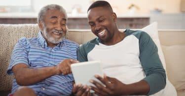 Homem jovem ensinando seu pai a usar o tablet.