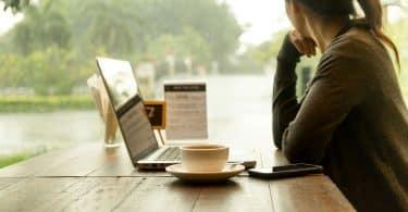 Mulher olhando para o lado com um laptop em sua frente aberto