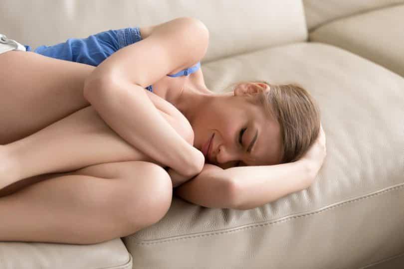 Mulher deitada no sofá em posição fetal chorando