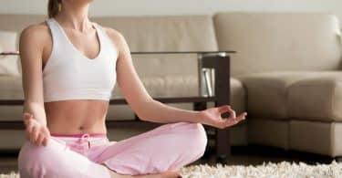 Mulher sentada no chão da sala de estar, meditando.