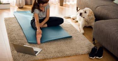 Mulher sentada no chão da sala de estar, alongando-se, ao lado de seu cachorro e de um laptop.