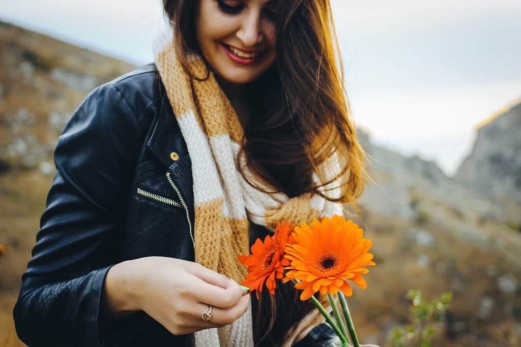 Mulher sorrindo segurando flor em meio a montanhas