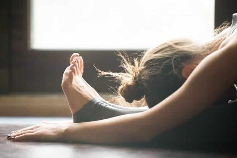 Mulher praticando Yoga com a cabeça sobre as pernas esticadas no chão.