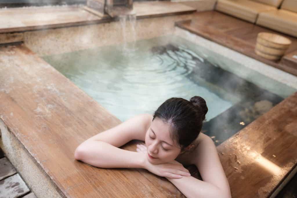 Imagem de uma mulher oriental dentro de uma banheira fazendo vaporização.