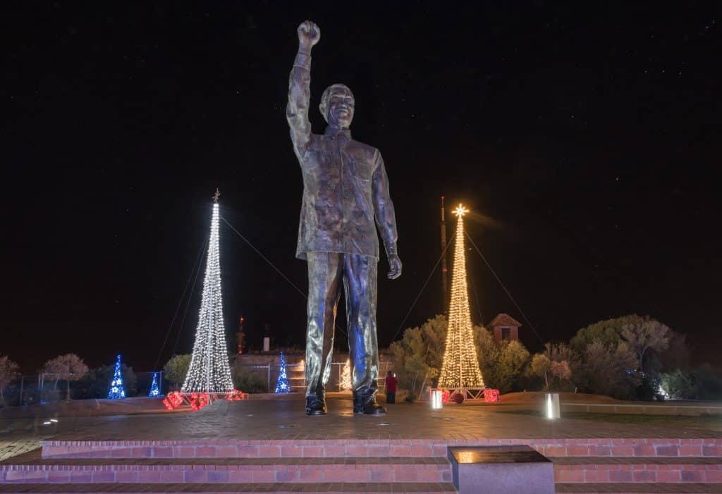 Imagem de uma estátua gigante de Nelson Mandela instalada em uma das praças da África. Ao lado da estátua duas árvores de Natal iluminadas.