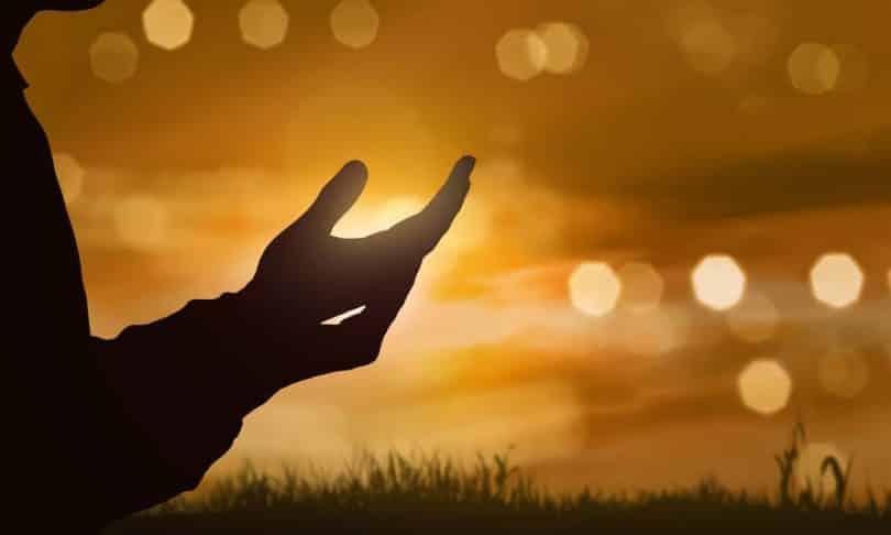 Silhueta de mãos com efeitos de luz ao fundo