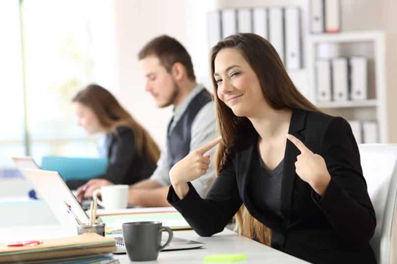 Mulher no trabalho sorrindo e apontando para si mesma