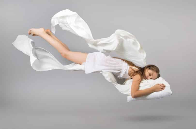 Mulher de vestido flutuando no ar enquanto dorme.