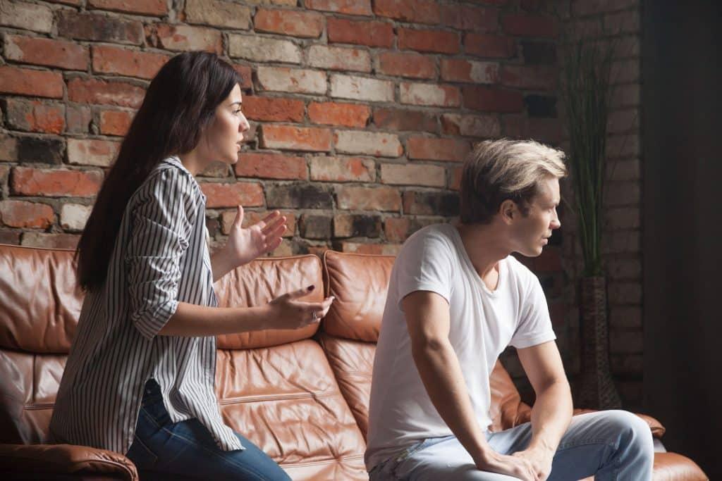 Mulher tenta discutir com um homem sentado no sofá, que a ignora.