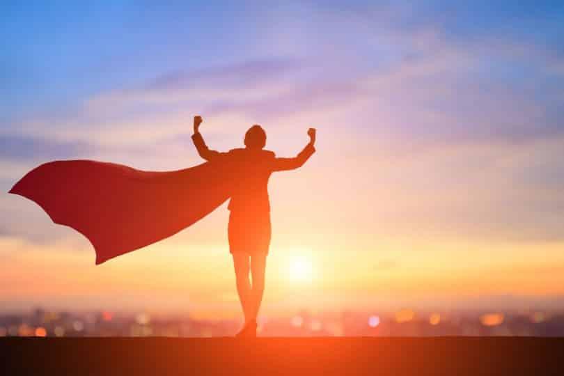 Silhueta de uma mulher com capa de super-heroína em frente ao pôr do sol.