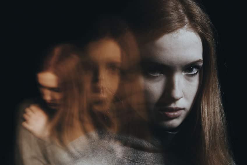 Mulher com várias imagens borradas de seu rosto com expressões diferentes, indicando confusão e mudanças de comportamento.