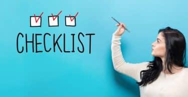 """Mulher segurando caneta, ao lado de três caixas desenhadas em uma parede, todas com tiques, e a palavra """"checklist"""" escrita embaixo."""